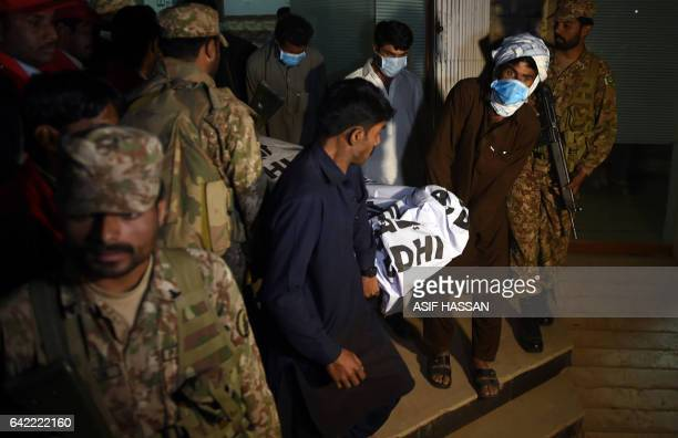 Pakistani soldiers stand guard as Pakistani volunteers carry the body of a victim from a local hospital in the town of Sehwan on February 17 a day...