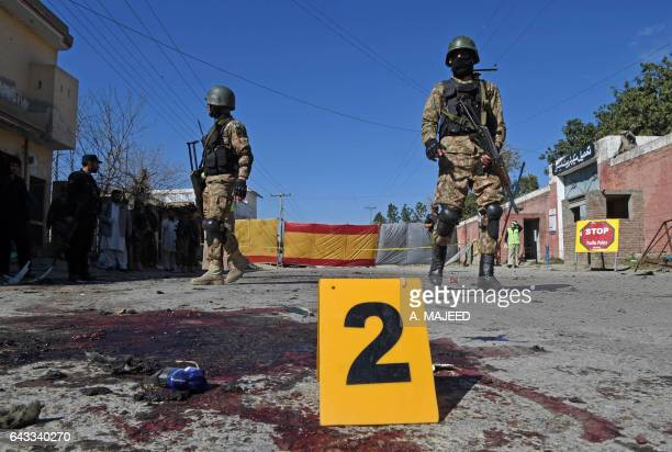 Pakistani soldiers stand guard at the site of a court complex after multiple Taliban suicide bomb attacks in the Tangi area of Charsadda district on...
