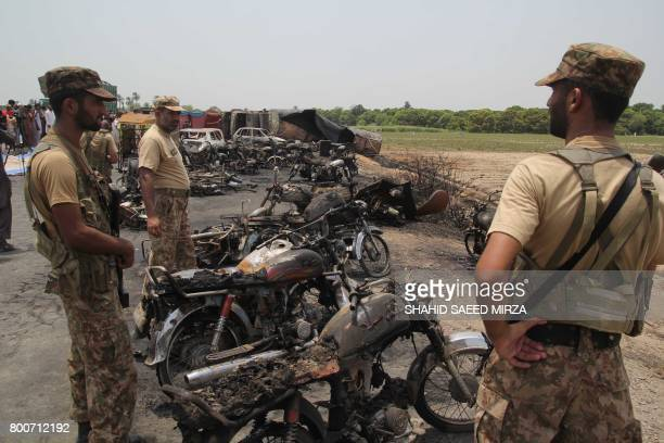 Pakistani soldiers stand guard beside burnt out vehicles at the scene where an oil tanker caught fire following an accident on a highway near the...