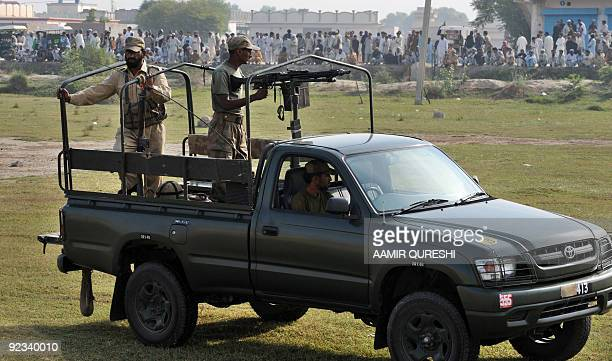 Pakistani soldiers stand guard from their pickup truck as they watch a queue of internally displaced Pakistani civilians fleeing from military...
