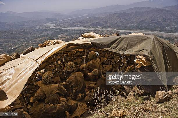Pakistani soldiers stand guard on top of a mountain overlooking Swat valley at Banai Baba Ziarat area in northwest Pakistan on May 22 2009 The army...