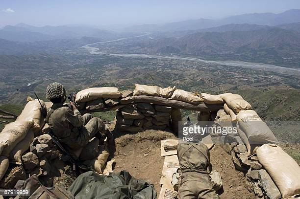 Pakistani soldiers stand guard on top of a mountain overlooking the Swat valley at Banai Baba Ziarat area on May 22 2009 in northwest Pakistan Troops...