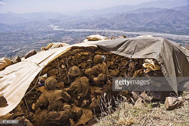 Pakistani soldiers stand guard on top of a mountain overlooking the Swat valley on May 22 2009 in theBanai Baba Ziarat area of northwest Pakistan...