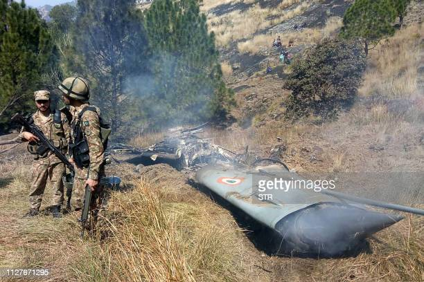TOPSHOT Pakistani soldiers stand next to what Pakistan says is the wreckage of an Indian fighter jet shot down in Pakistan controled Kashmir at...