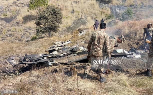 Pakistani soldiers stand next to what Pakistan says is the wreckage of an Indian fighter jet shot down in Pakistan controled Kashmir at Somani area...
