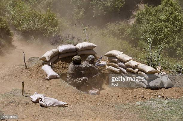 Pakistani soldiers take cover as a helicopter takes off from the top of a mountain on May 22 2009 at Banai Baba Ziarat area in northwest Pakistan...