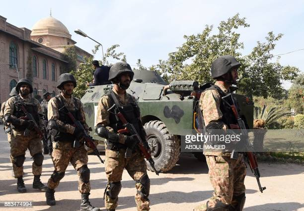 Pakistani soldiers walk at the premises of an Agriculture Training Institute after an attack by Taliban militants in Peshawar on December 1 2017 Nine...