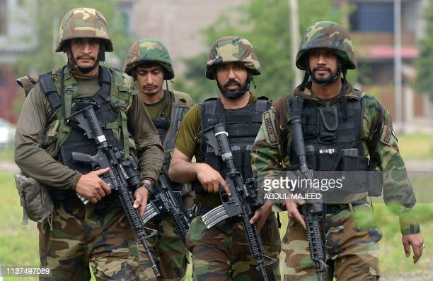 Pakistani soldiers walk from a site after an operation against suspected militants in Peshawar on April 16 2019 An entire threestorey building was...