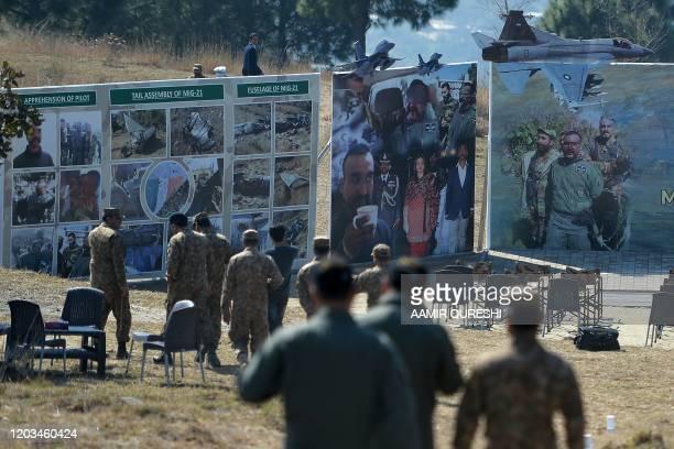 Pakistani soldiers walk near images of captured Indian pilot wing commander Abhinandan Varthaman at Horran village where Varthaman's Mig21 fighter...