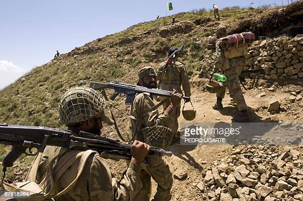 Pakistani soldiers walk to their positions on top of a mountain at Banai Baba Ziarat area in northwest Pakistan on May 22 2009 The army took control...