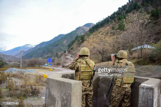 Pakistani soldiers watch over potential Indian troop movements with binoculars in a bunker at the Chakothi post some 52 kms from Muzaffarabad near...