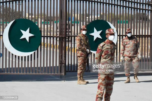 Pakistani soldiers wear facemasks on the closed border of Pakistan-Iran in Taftan on February 25, 2020 as fears over the spread of the COVID-19...