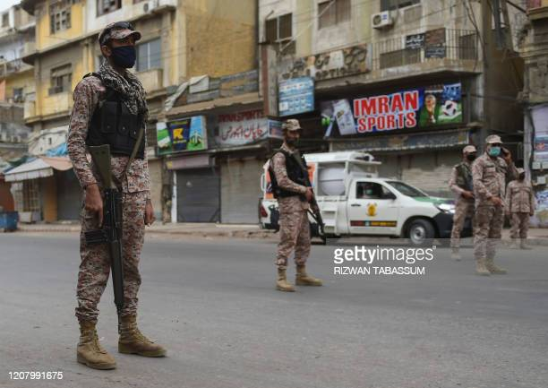 Pakistani soldiers wearing facemasks stand guard on a deserted street during a lockdown after Sindh province government announced the closing of...