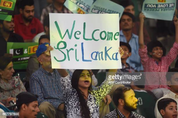 Pakistani spectator holds a placard while cheering during the T20 cricket match between Pakistan and Sri Lanka at the Gaddafi Cricket Stadium in...