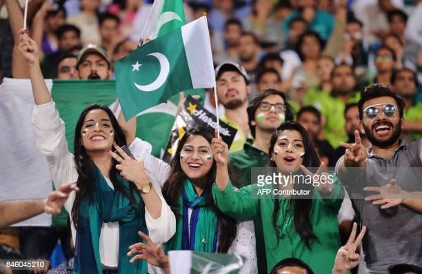 Pakistani spectators cheer as they watch the first Twenty20 international match between the World XI and Pakistan at the Gaddafi Cricket Stadium in...