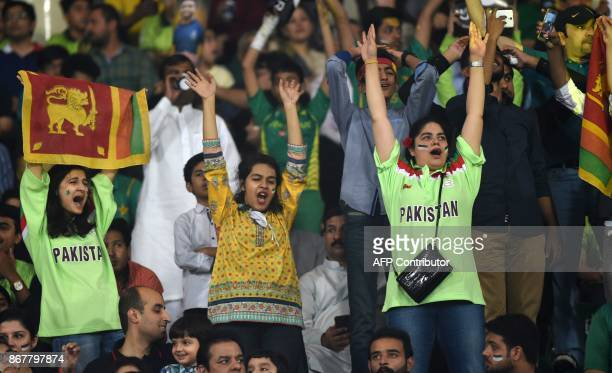 Pakistani spectators cheer during the T20 cricket match between Pakistan and Sri Lanka at the Gaddafi Cricket Stadium in Lahore on October 29 2017...