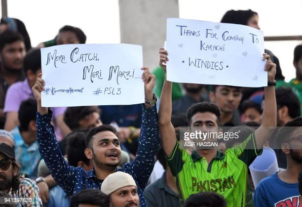Pakistani spectators hold placards at the National Cricket Stadium before start the third and final Twenty20 International cricket match between...