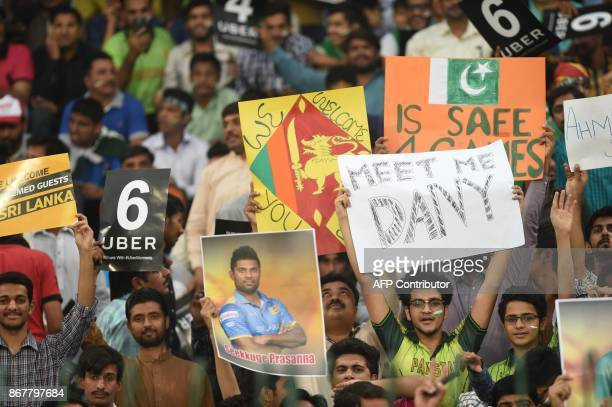Pakistani spectators hold placards during the T20 cricket match between Pakistan and Sri Lanka at the Gaddafi Cricket Stadium in Lahore on October...