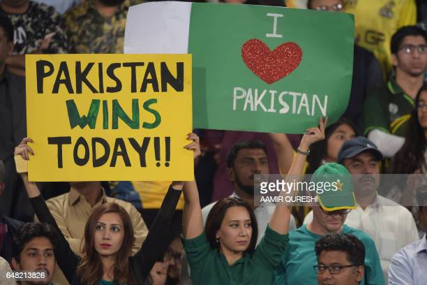 Pakistani spectators hold placards prior to the start of the final cricket match of the Pakistan Super League between Quetta Gladiators and Peshawar...