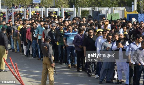 Pakistani spectators queue at one of entry gate of The Gaddafi Cricket Stadium in Lahore on March 5 as they arrive to watch the final cricket match...