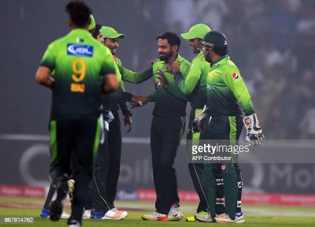 Pakistani spinner Mohammad Hafeez celebrates with teammates after the dismissal of an Sri Lankan cricketer during the third and final T20 cricket...