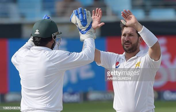 Pakistani spinner Yasir Shah celebrates with captain Sarfraz Ahmed after the dismissal of New Zealand batsman Jeet Raval during the third day of the...