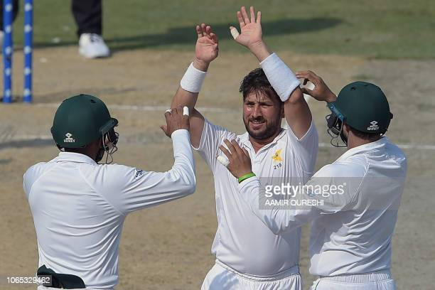 Pakistani spinner Yasir Shah celebrates with teammates after taking the wicket of New Zealand batsman Neil Wagner during the third day of the second...
