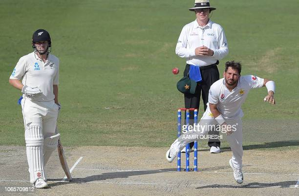 Pakistani spinner Yasir Shah delivers the ball as New Zealand batsman Henry Nicholls looks on during the fourth day of the second Test cricket match...