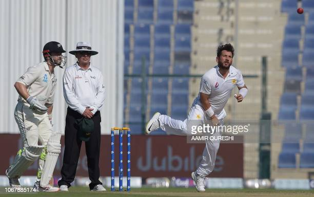 Pakistani spinner Yasir Shah delivers the ball as New Zealand captain and batsman Kane Williamson looks on during the first day of the third and...