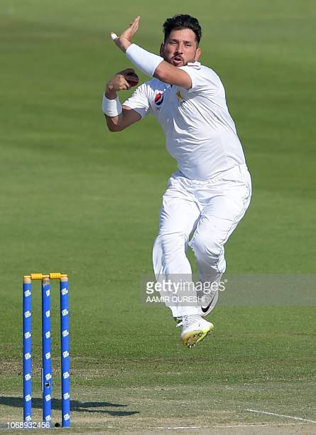 Pakistani spinner Yasir Shah delivers the ball as New Zealand captain Kane Williamson looks on during the fourth day of the third and final Test...