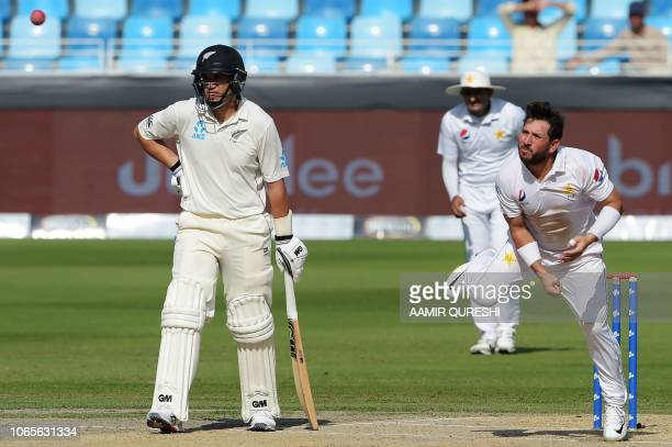 Pakistani spinner Yasir Shah delivers the ball next to New Zealand batsman Ross Taylor during the fourth day of the second Test cricket match between...