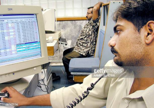 A Pakistani stock broker talks on telephone as his colleague sits relaxed at the Karachi Stock Exchange 20 June 2003 in Karachi The benchmark KSE100...