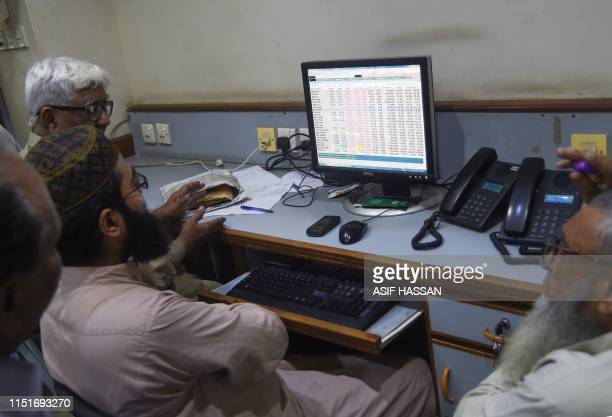Pakistani stock brokers monitor share prices on a computer monitor during a trading session at the Pakistan Stock Exchange in Karachi on June 24 2019
