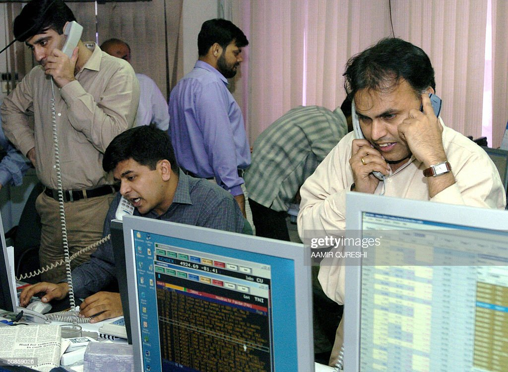 Pakistani stock brokers watch computer teminals as they communicate by telephone with their clients at a brokerage house in Karachi, 20 May 2004. The benchmark Karachi Stock Exchange, KSE-100 index rose 39 points to close 5477.73 points as investors welcomed the news of incoming Indian Prime Minister Manmohan Singh's pledge to push forward a peace dialogue with Islamabad, analysts said. AFP PHOTO/ Aamir QURESHI