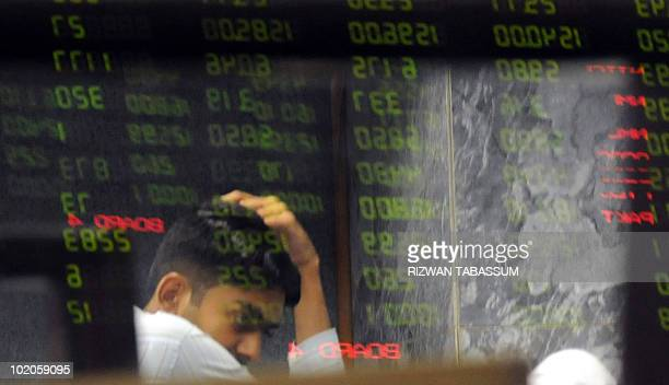 A Pakistani stockbroker is reflected in an index board as he reacts during a trading session at the Karachi Stock Exchange on June 14 2010 The...