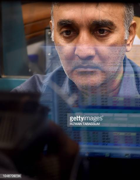 A Pakistani stockbroker looks at share prices on a computer monitor during a trading session at the Pakistan Stock Exchange in Karachi on October 10...