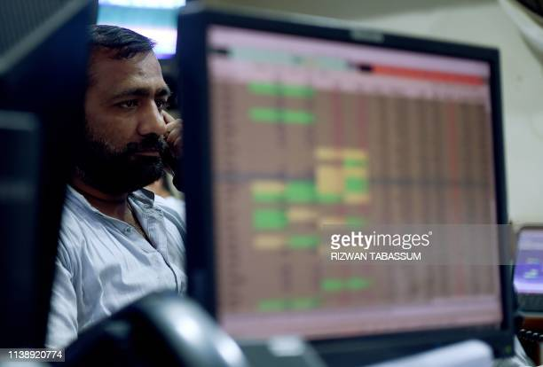 A Pakistani stockbroker looks at share prices on a computer monitor during a trading session at the Pakistan Stock Exchange in Karachi on April 23...
