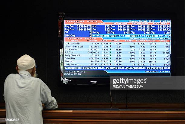 A Pakistani stockbroker looks at the latest share prices on a digital board during a trading session at the Karachi Stock Exchange in Karachi on May...
