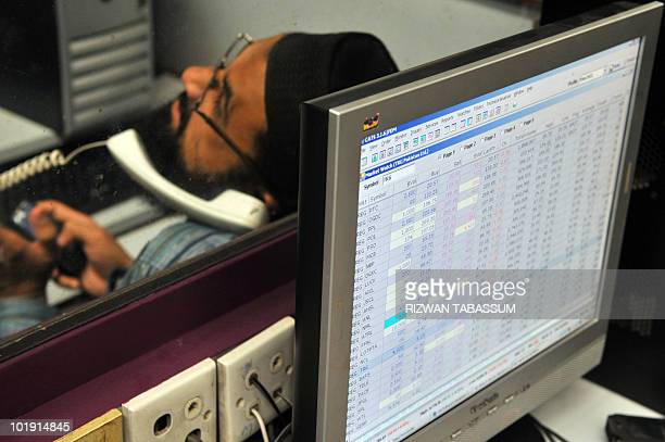 A Pakistani stockbroker monitors share prices during a trading session at the Karachi Stock Exchange on June 9 2010 The benchmark KSE100 index was...
