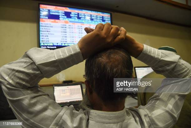 A Pakistani stockbroker monitors share prices during a trading session at the Pakistan Stock Exchange in Karachi on April 17 2019