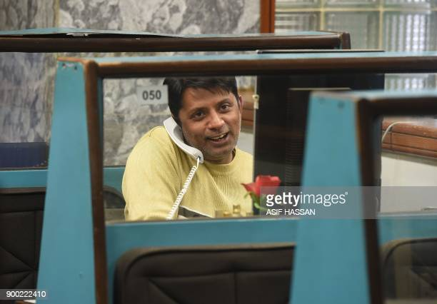A Pakistani stockbroker monitors shares as talking on phone during a trading session at the Pakistan Stock Exchange in Karachi on January 1 2018 /...