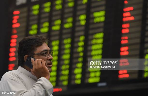 A Pakistani stockbroker talks on a phone as he watches the latest share prices during a trading session at the Pakistan Stock Exchange in Karachi on...