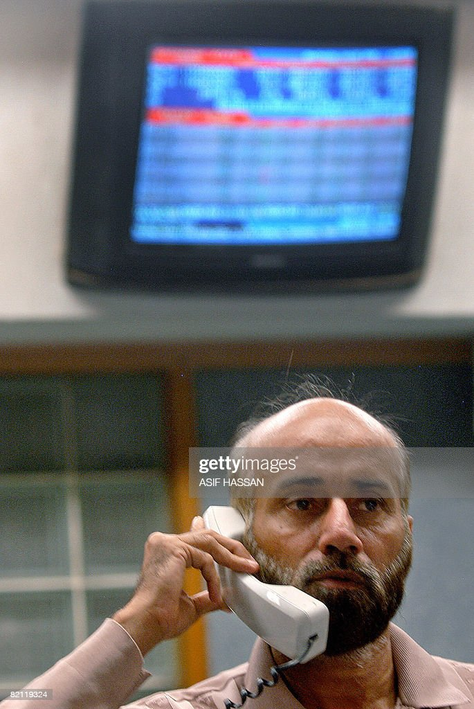 A Pakistani Stockbroker Talks On Telephone As Watches Share Price Monitor At The Main