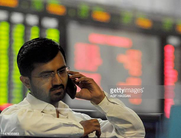 A Pakistani stockbroker talks on his cell phone as he watches the latest share prices on a digital board during a trading session at the Karachi...