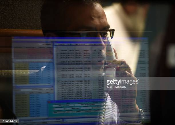 Pakistani stockbroker talks on his phone during a trading session at the Pakistan Stock Exchange in Karachi on March 7 2016 / AFP / ASIF HASSAN