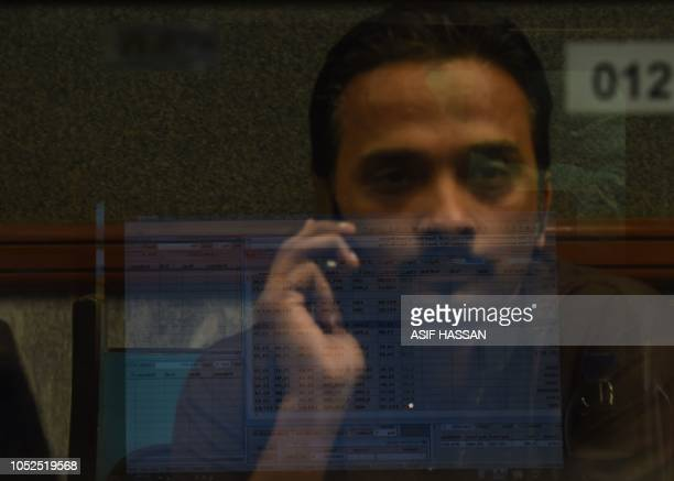 A Pakistani stockbroker talks on phone as he watches the latest share prices on a monitor during a trading session at the Pakistan Stock Exchange in...
