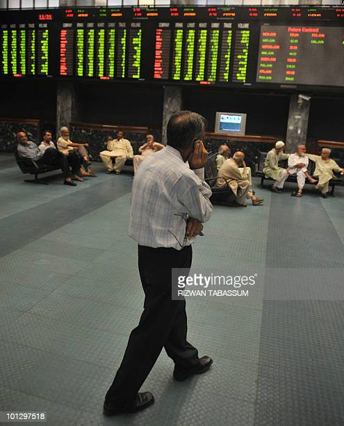 A Pakistani stockbroker talks on phone during a trading session at the Karachi Stock Exchange on May 31 2010 The benchmark 100 index was 937783 down...