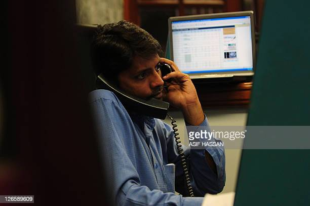 A Pakistani stockbroker talks on telephones as he monitors latest share prices during a trading session at the Karachi Stock Exchange in Karachi on...