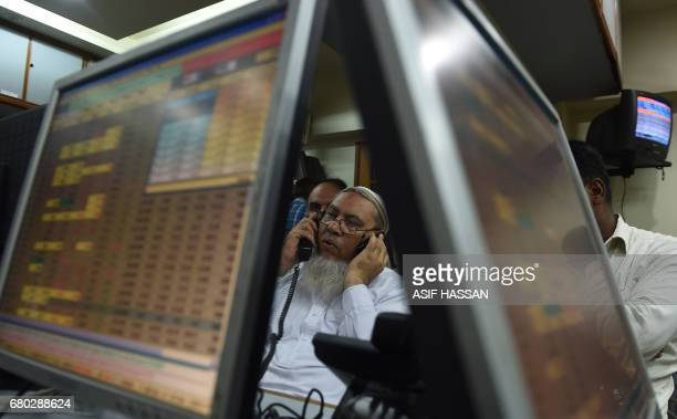 A Pakistani stockbroker talks on the phone during a trading session at the Pakistan Stock Exchange in Karachi on May 8 2017 The benchmark PSE100Index...
