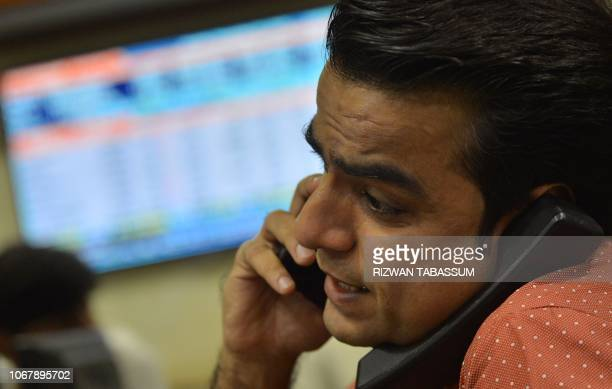A Pakistani stockbroker talks on the phone while monitoring share prices during a trading session at the Pakistan Stock Exchange in Karachi on...